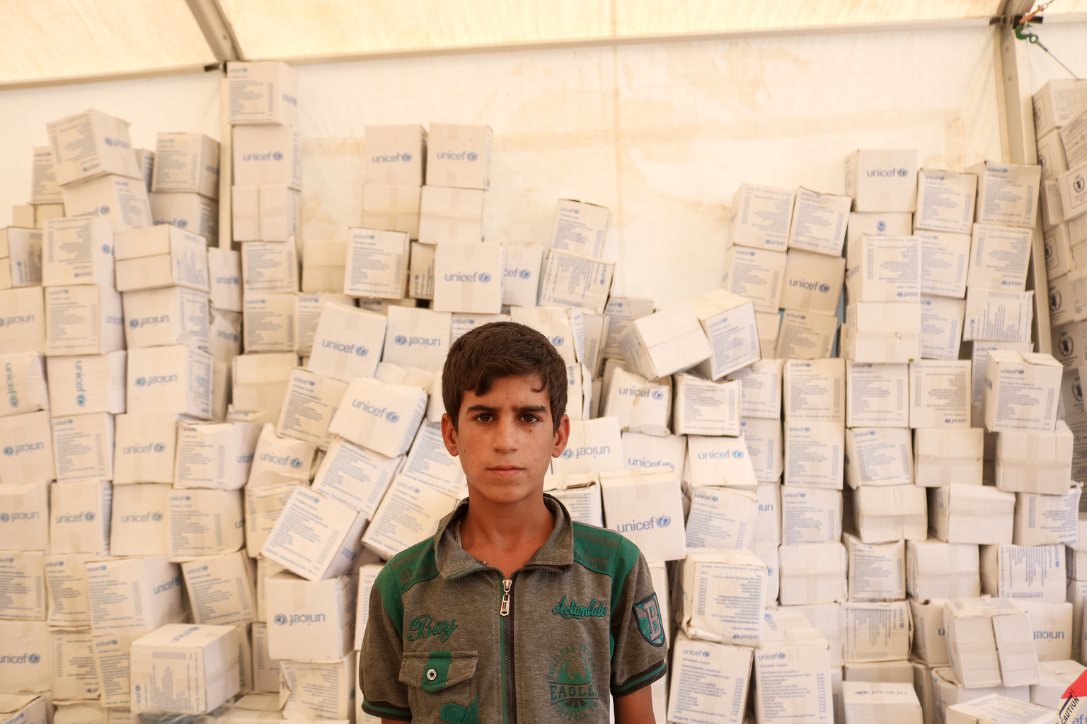 A boy in a green shirt stands in front of piled up boxes.