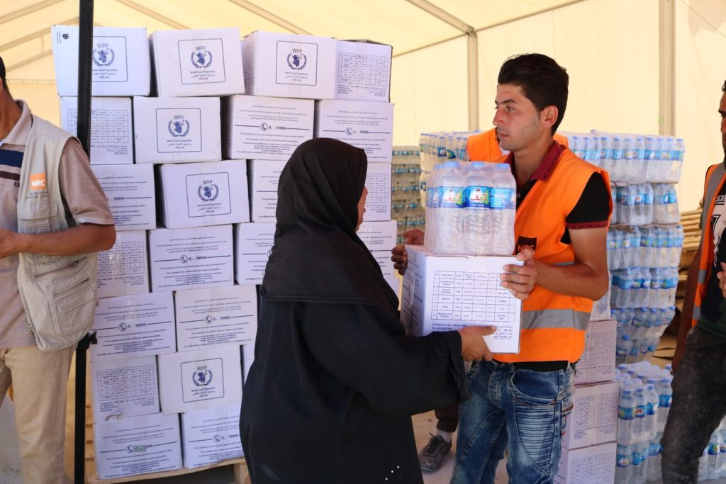 A man in an orange vest hands a woman in a black abaya a box of supplies and a pack of bottled water