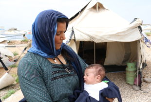 A woman in a blue headscarf holds a baby outside a tent.