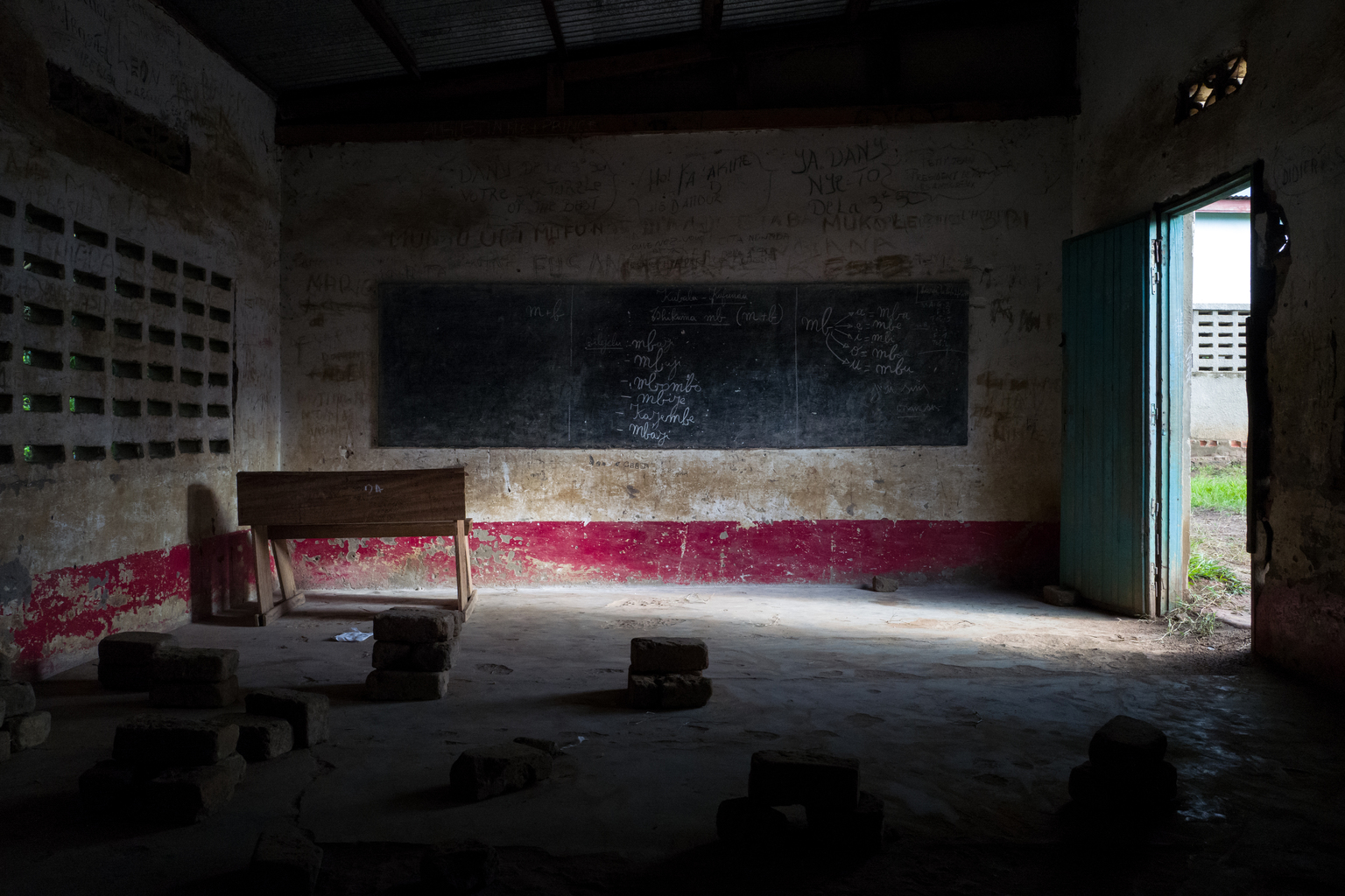 A shaft of light reflects an empty classroom with an empty chalkboard.