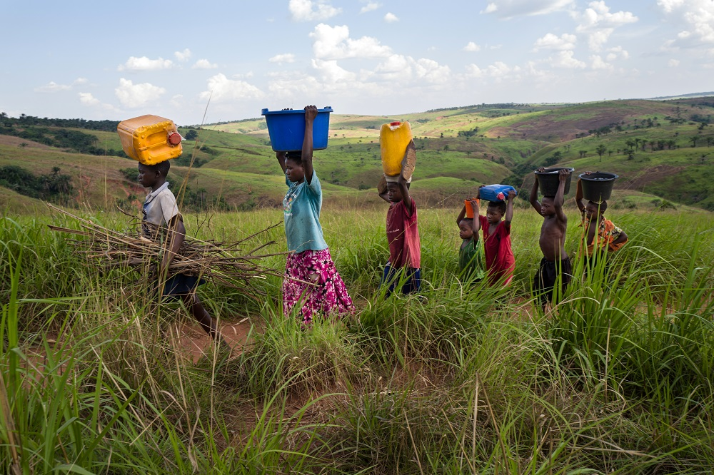 Six girls carrying buckets on their heads walk across a green field with rolling hills in the background.
