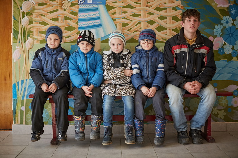 Five children in winter clothing sit on a bench.