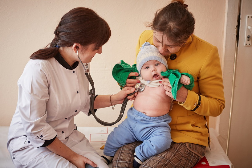 A health worker puts a stethoscope against the bare chest of a baby while his mother holds him.