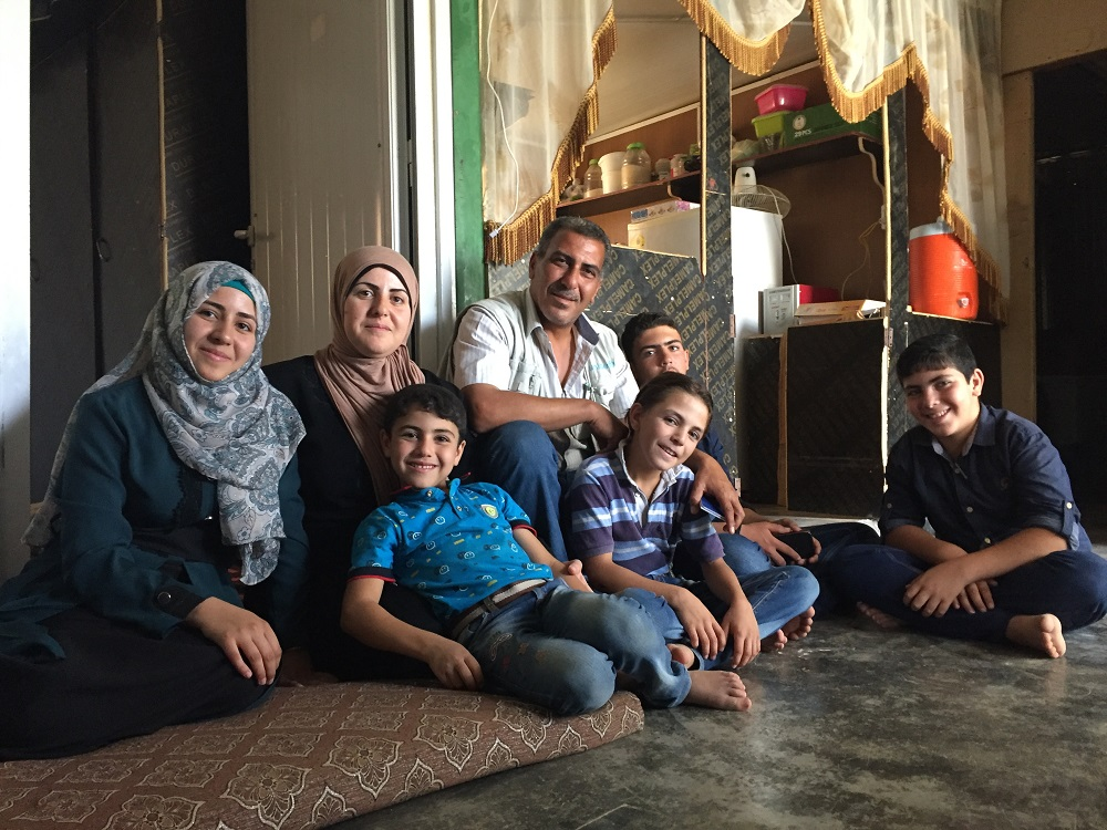 A mother, father and four children sit on the floor in a caravan.