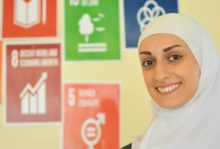 A young woman in a white hijab smiles for the camera