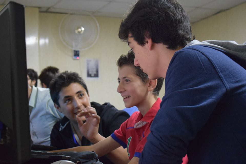Three young men smile as they look at a computer screen.