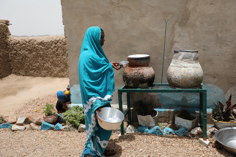 A woman in a blue hijab takes water from a clay vessel