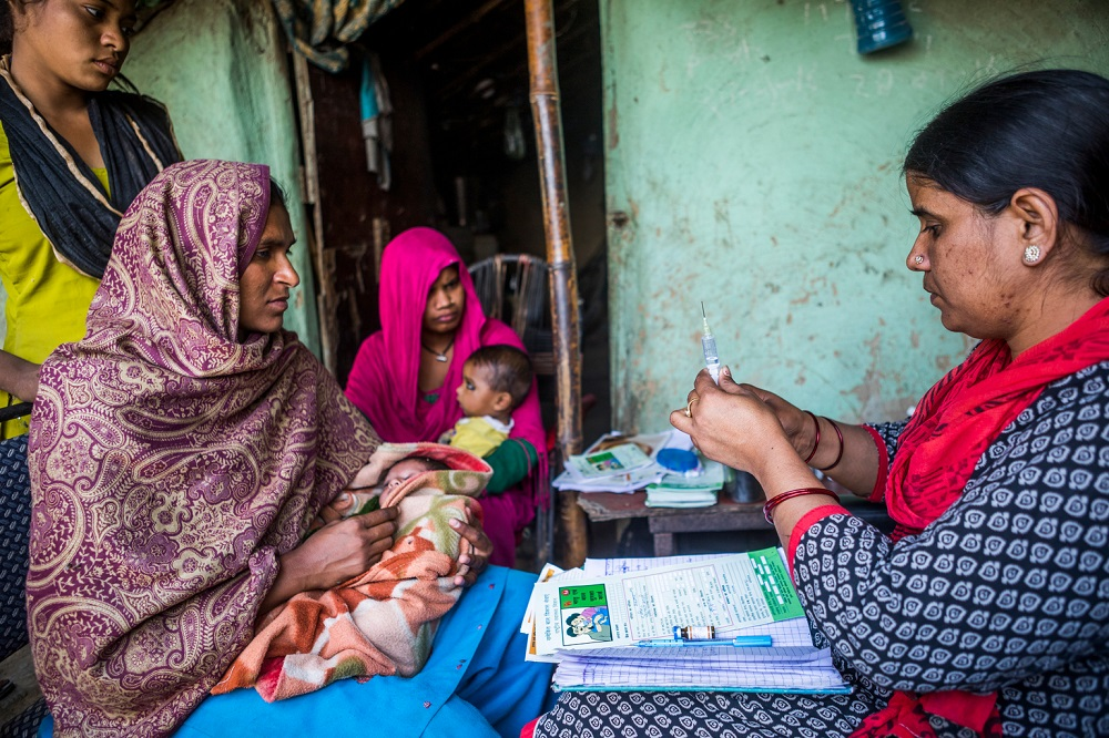 A mother holding a young baby sits opposite a health worker preparing a vaccination needle.