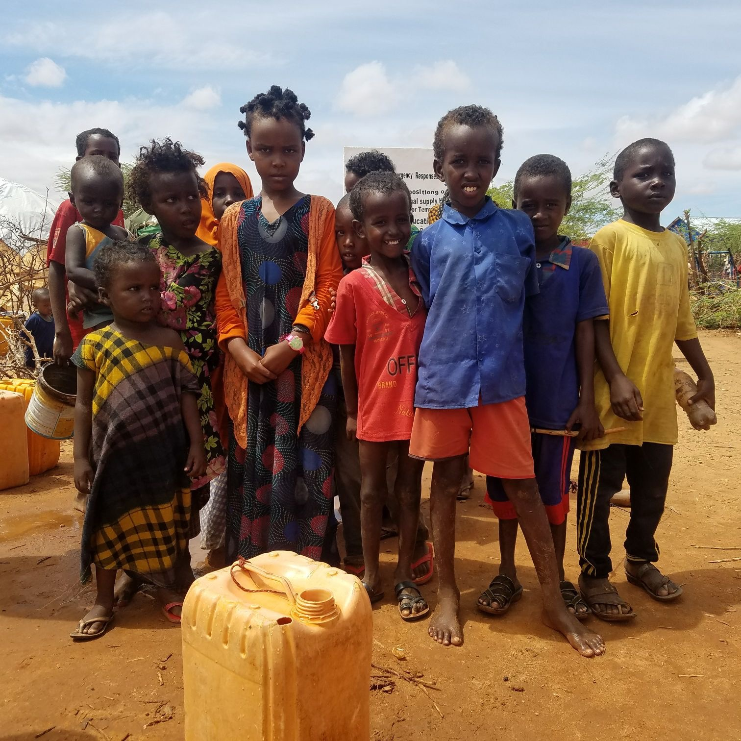 A group of children in brightly coloured clothing stand in front of a jerry can