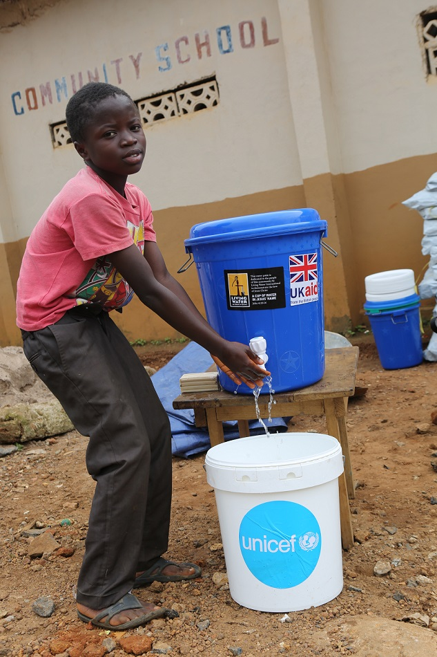 A young boy washed his hands at a bucket with spout.