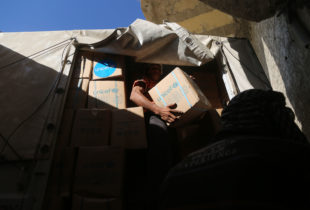 A man unloads UNICEF-branded box out of a covered truck.