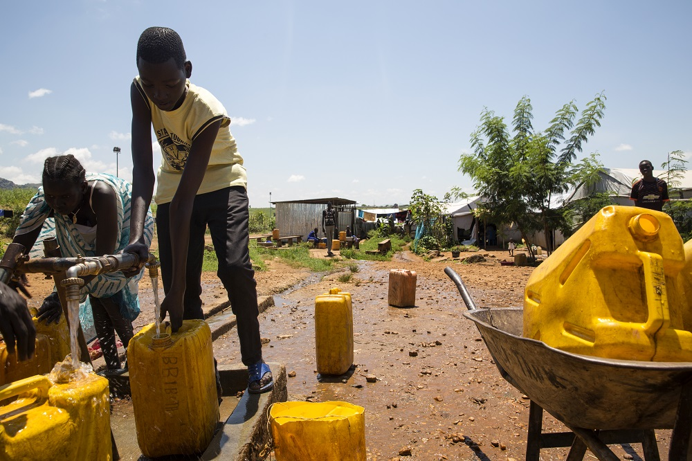 A boy in a white shirt pumps water into a yellow jerry can.