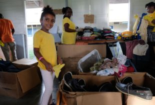 A girl dressed in yellow smiles in front of a box of shoes.
