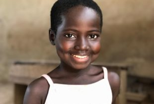A girl in a white shirt smiles for the camera.
