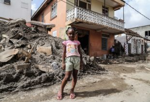 Hurricane Maria: A young girl in short stands in front of her flooded home