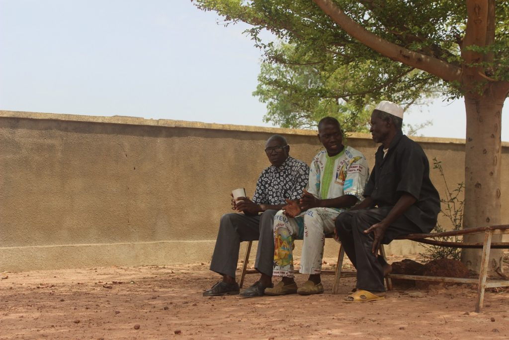 Three men sit on a bench under a tree.