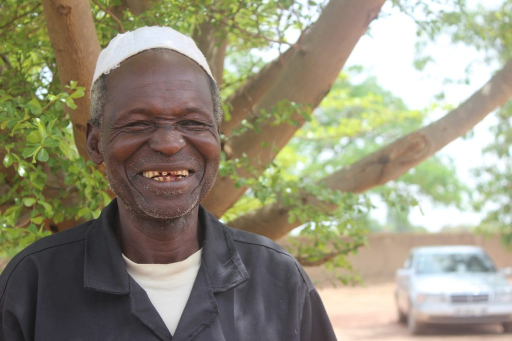 A muslim man wearing a white cap smiles for the camera.