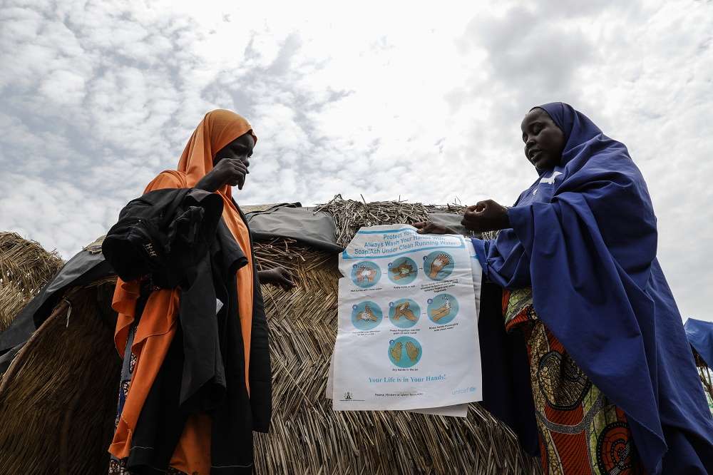 A woman holds a poster as she speaks to another woman about cholera.