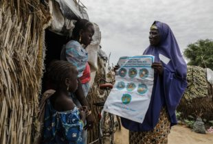 A woman holding a poster speaks to another woman who's standing outside a hut.