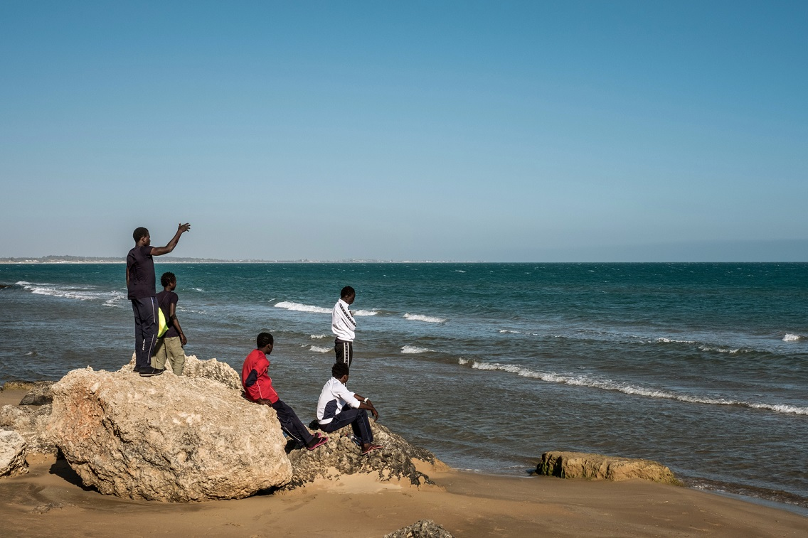 A group of boys from Gambia sitting on a large rock by the sea in Sicily