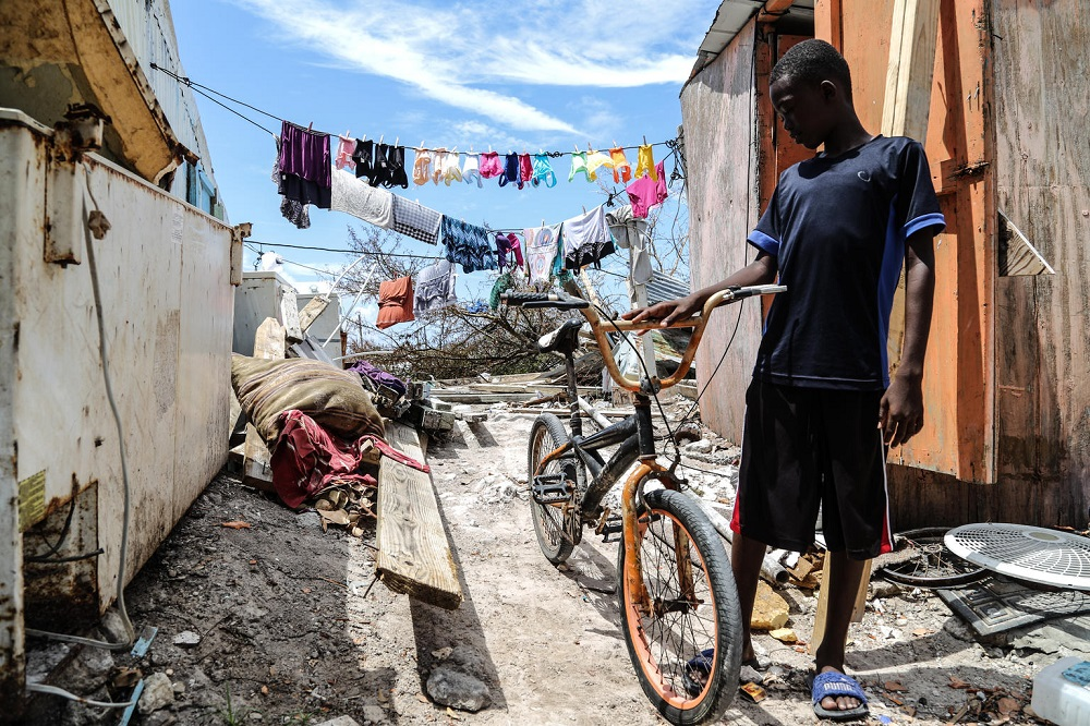 A boy, surrounded by hurricane devastation, holds his bicycle with one hand.