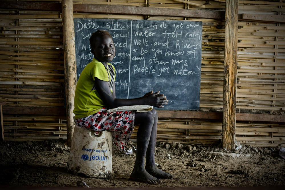 A girl sits on a UNICEF bucket in a classroom with a blackboard on the wall.