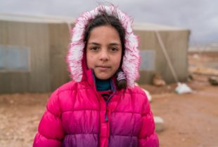 A young refugee girl in a pink fur-lined jacket stands in front of a building.