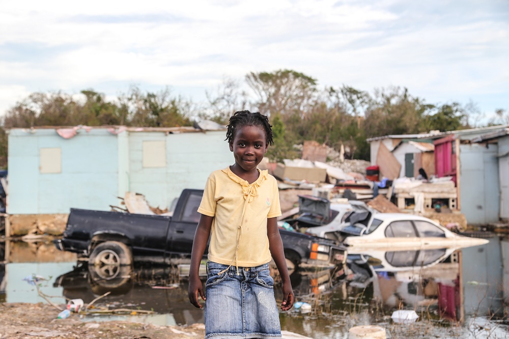 A girl in a yellow shirt stands in front of a pile of hurricane wreckage