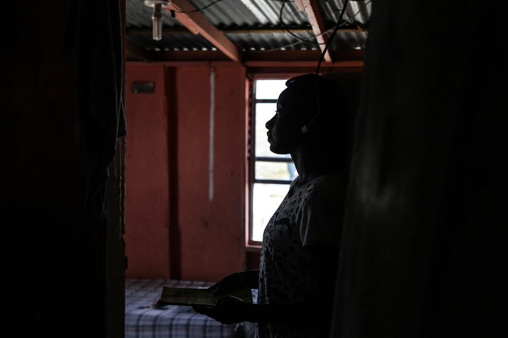 A young woman stands in a dark room, her profile sillouetted against an open window.
