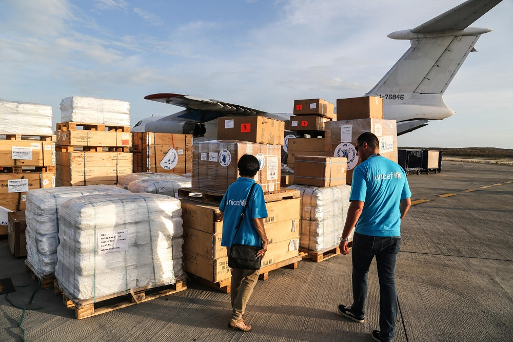 A woman and a man, both dressed in UNICEF shirts, walk towards a stack of supplies on a tarmac.