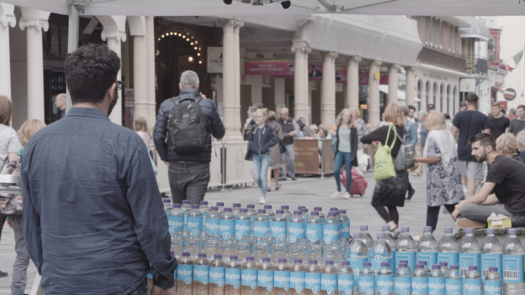 Bottles of water are lined up on a table in the middle of a town square.