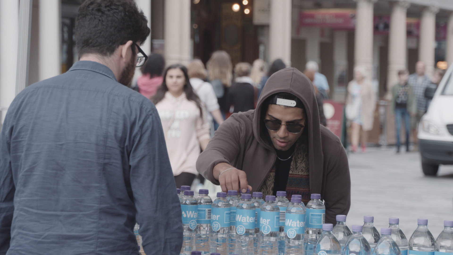A man in a hoodie reaches for a bottle of water while a man in a grey shirt looks on.