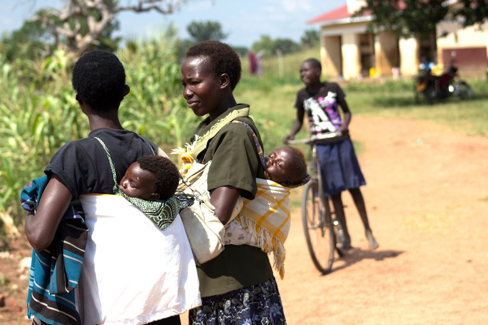 Two women carry their babies in a sling on their backs.