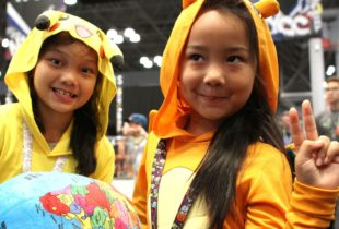 Two girls dressed as Pokemon characters in yellow smile for the camera.