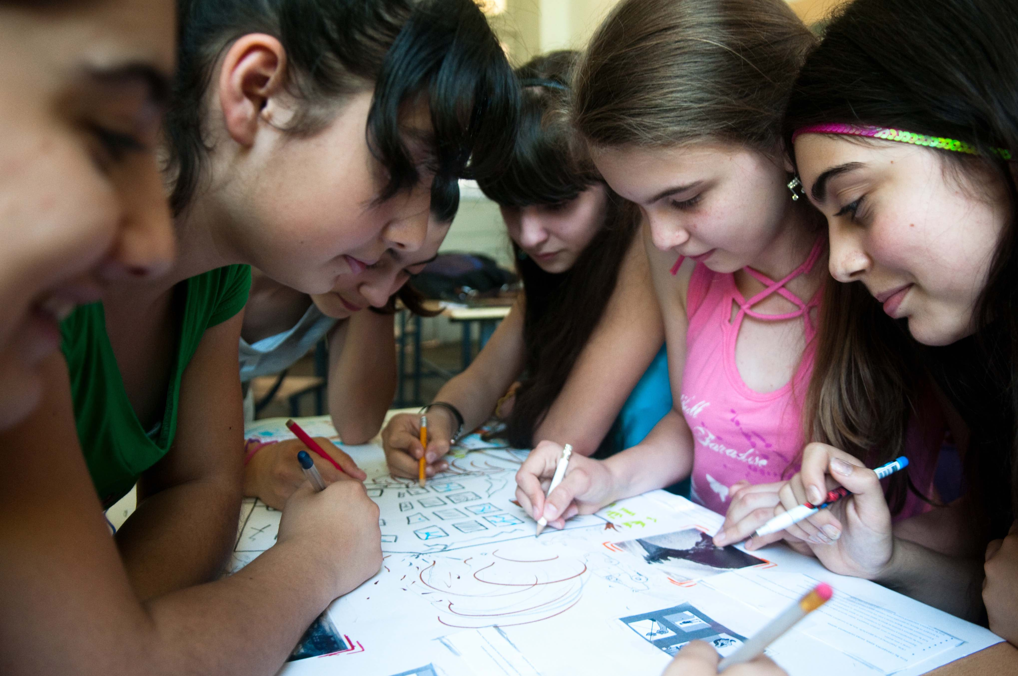 Girls working on a poster together.
