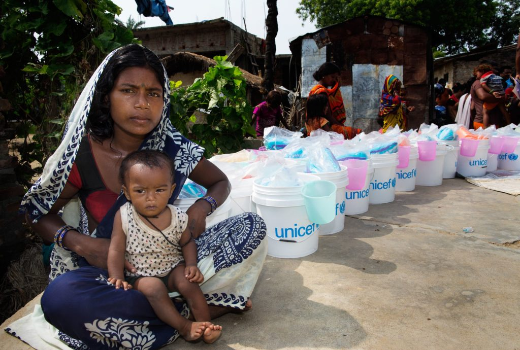A womand sits on the ground with her child, with a row of UNICEF buckets in the background