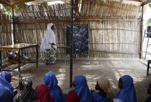 A girl in a white head covering stands at the front of a classroom.