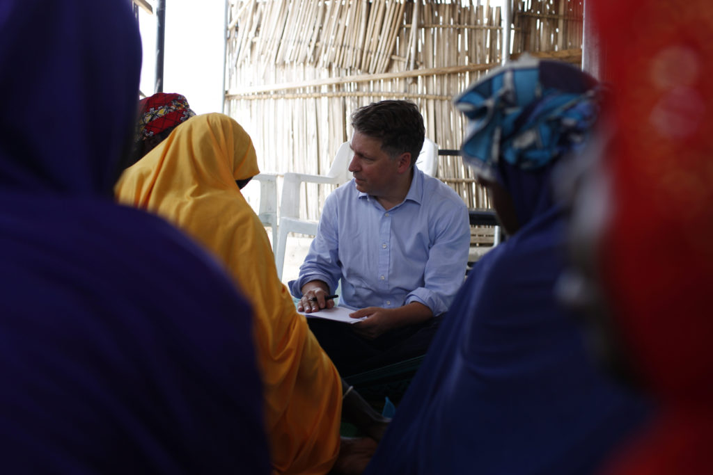 A man in a blue shirt sits surrounded by women in colourul headscarves.