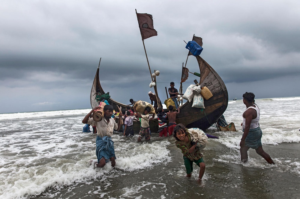 Several people. carrying belongings, get out of a boat which is moored close to shore.