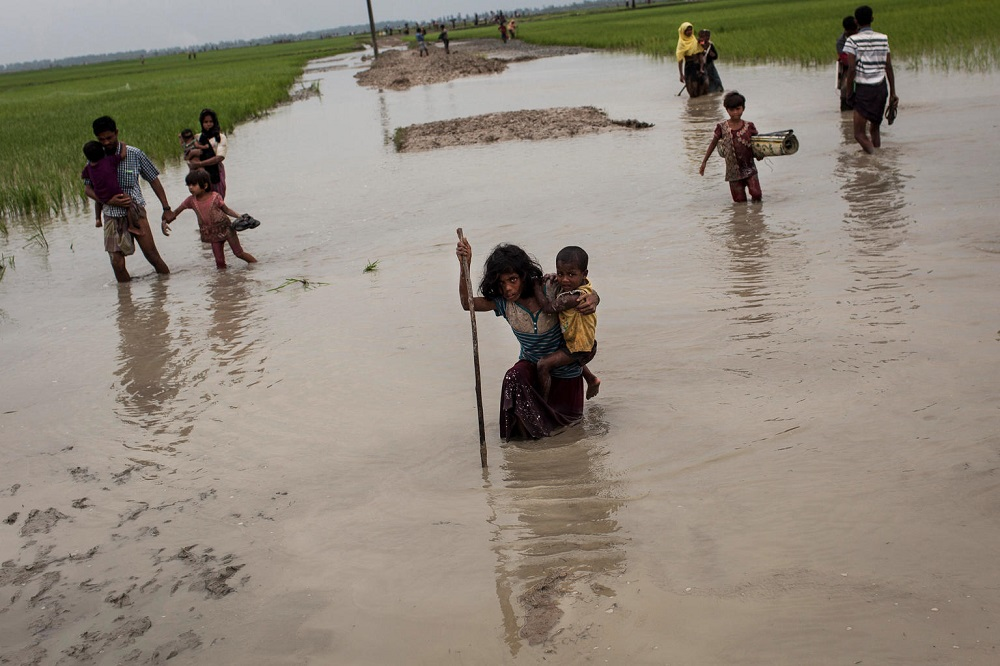 A girl walks through deep water carrying a stick and a young child.