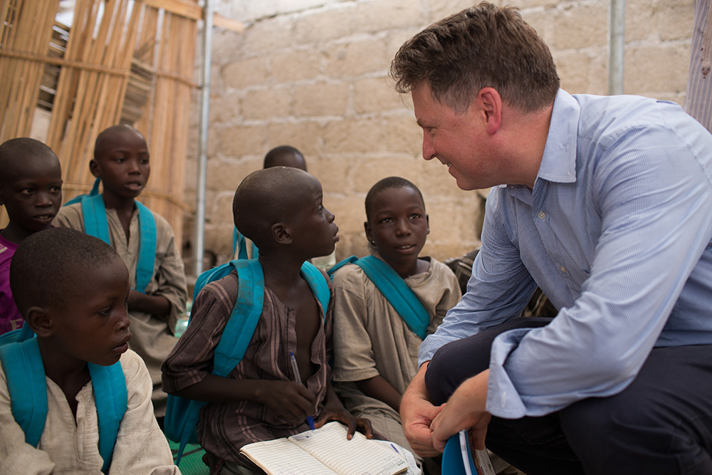 A man in a blue shirt talks to boys who wear UNICEF backpacks.