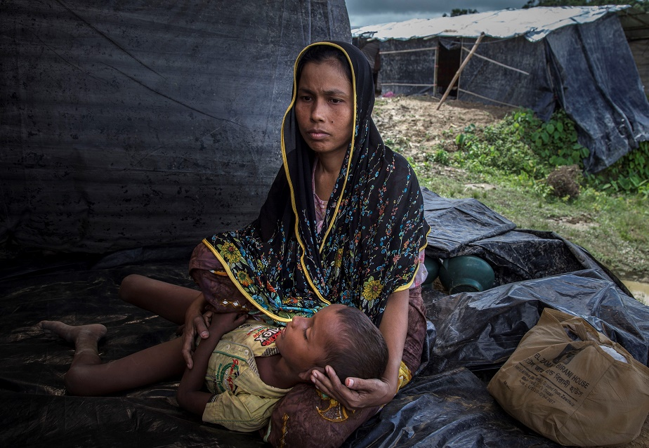 A Rohingya woman sits on the ground in Bangladesh with her child in her arms