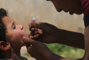 A boy receiving a drop of vaccine on his tongue.