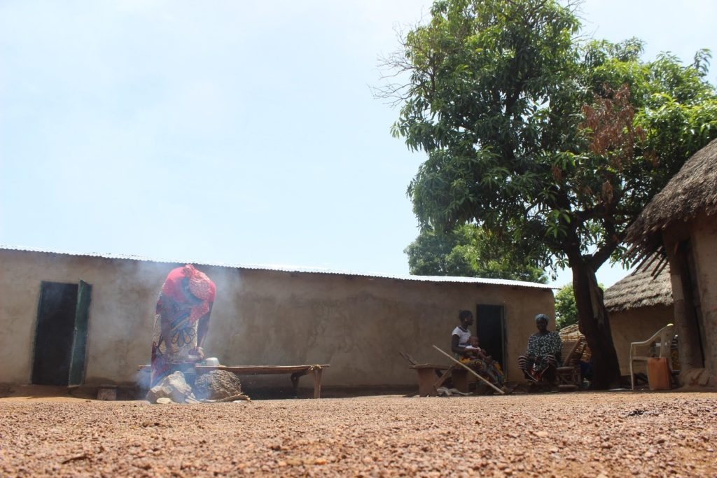In the middle of a large compound a woman bends over a small fire.