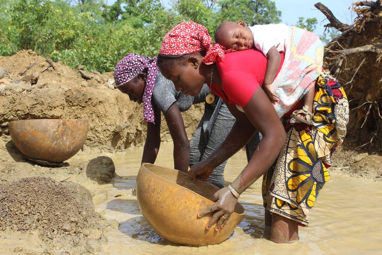 Two women, one with a baby on her back, hold a container while bending over slurry.