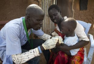 A health worker wearing gloves examines a young child who sits on his mother's lap.
