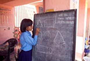 A young girl stands at a chalkboard.
