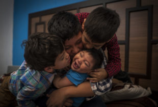 A little boy getting kissed by his 3 brothers