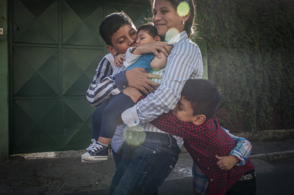 A boy in his mom's arms with his brothers alongside