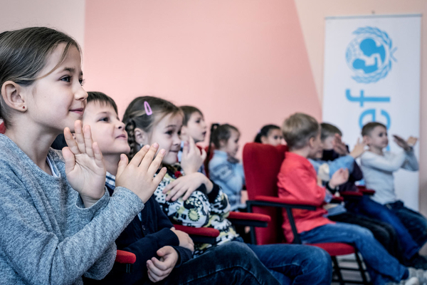 A group of children, listening carefully in their seats.